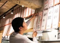 大衆酒場アオギリ 壁に貼るメニューは、その日の仕入れ状況により、スタッフの手で書いています。ちなみに貼っているのがオーナーです。